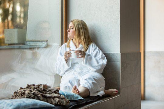 Frau im Bademantel mit einer Tasse Tee