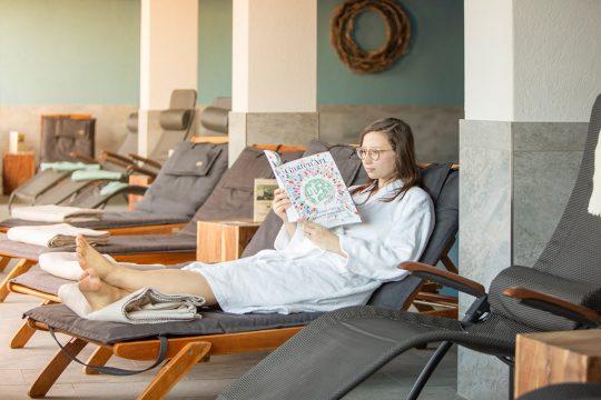 Frau mit Buch auf Liege